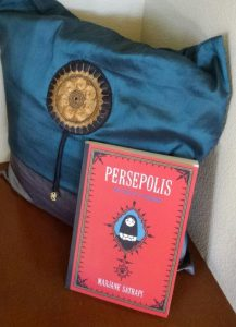 "Marjane Satrapi's comic novel ""Persepolis"" with a Persian-style pillow"