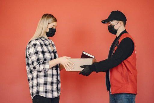 Livreur livre colis à une cliente avec masque et gants