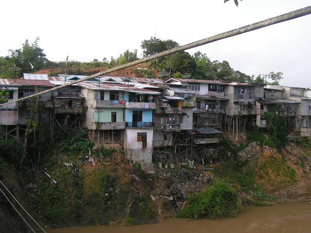 Houses perched between a road and the river.