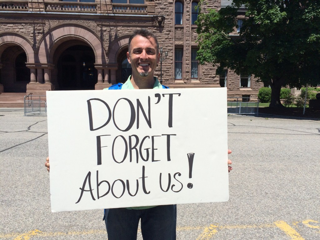Man holding sign that says Don't Forget About Us