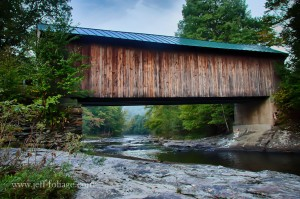 a side view of the fall foliage down the river under the Waterville covered bridge