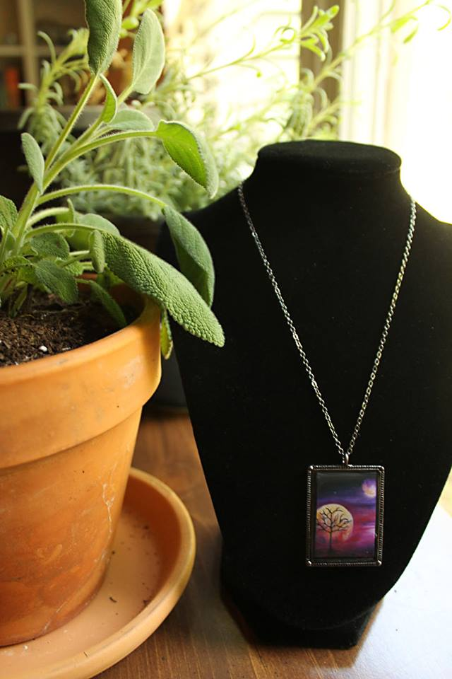Necklace of tree in front of moon with planet in distance. Colors are vivid purple, pink and gold. Painted by Jeffcoat Art and made into jewelry for purchase.