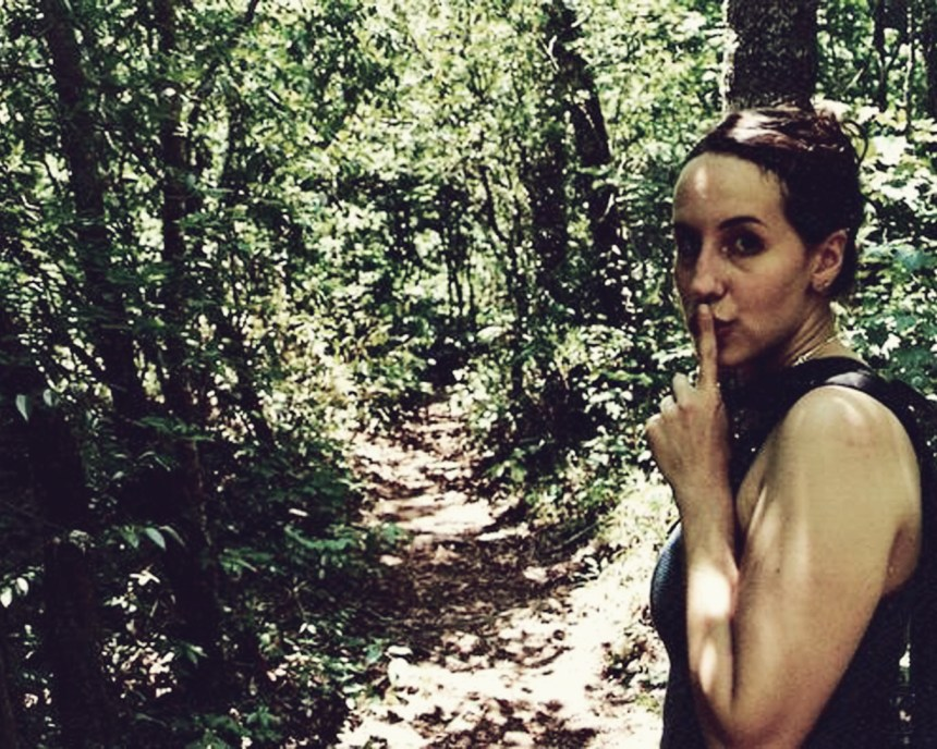 female artist hiking in woods to Panther Creek, GA