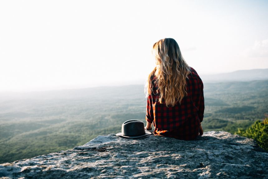 woman sitting on cliff in sunlight 7 Quick Ways to Get Inspired