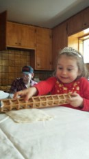 Maezy Smith learns how to roll out raviolis with her mom and great-grandfather.