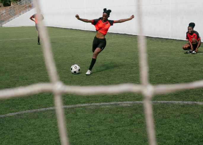 girl in red shirt and black shorts kicking a soccer ball