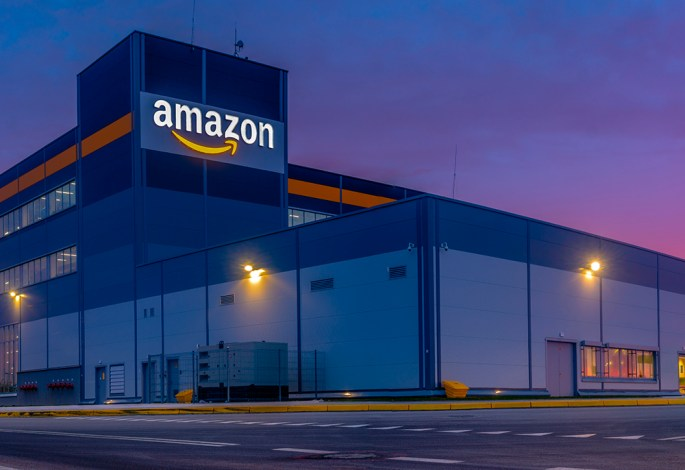 amazon distribution center with big amazon logo lit up on the side of the building at night