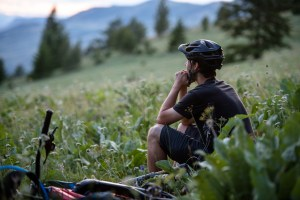 Mountain biker takes a break in a field, Kamloops B.C.