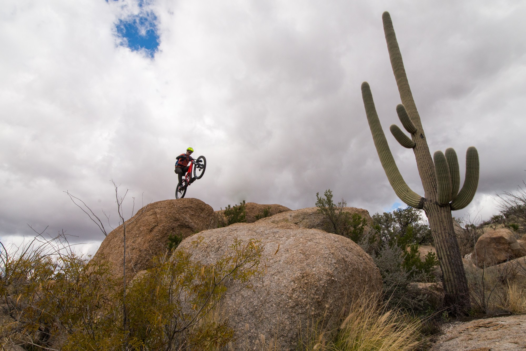 Jeff making a jump off a rock with a large saguaro cactus in the foreground and looming storm clouds above.
