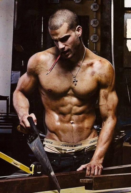 photo of shirtless man holding saw cutting boards
