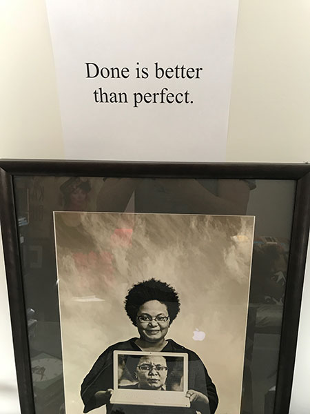 "The phrase ""Done is better than perfect"" taped to the wall above a photo of my friend Pamela, a Black woman smiling and holding a laptop that displays her face giving the viewer side-eye."