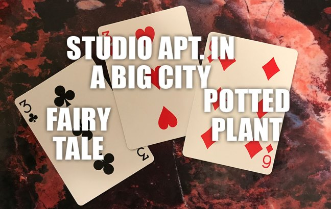 "Photo of three playing cards for the writing prompt ""Fairy tale, set in a studio apartment in a big city, containing a potted plant"""