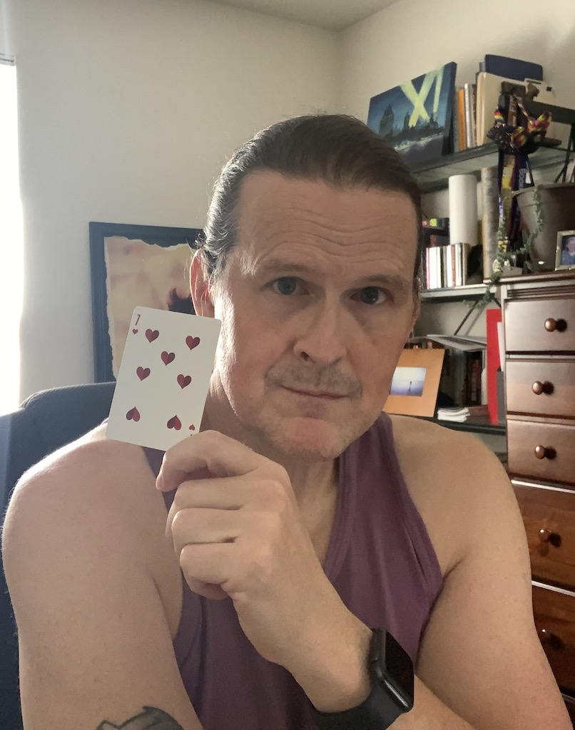 A white male (me) holding a playing card, specifically the seven of hearts.