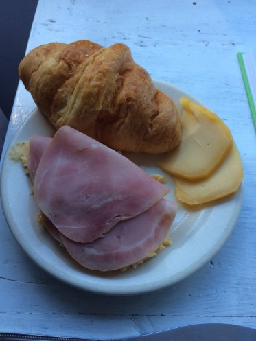 Monday's breakfast at home of scrambled eggs, ham, croissant, cheese.
