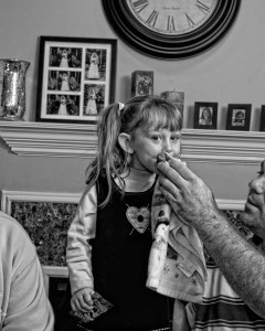 Father wipes his daughters mouth.
