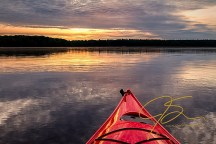 Watching the sunrise from my bright red kayak, the bow shown in the photo as the sun peeks through the clouds over the lake.