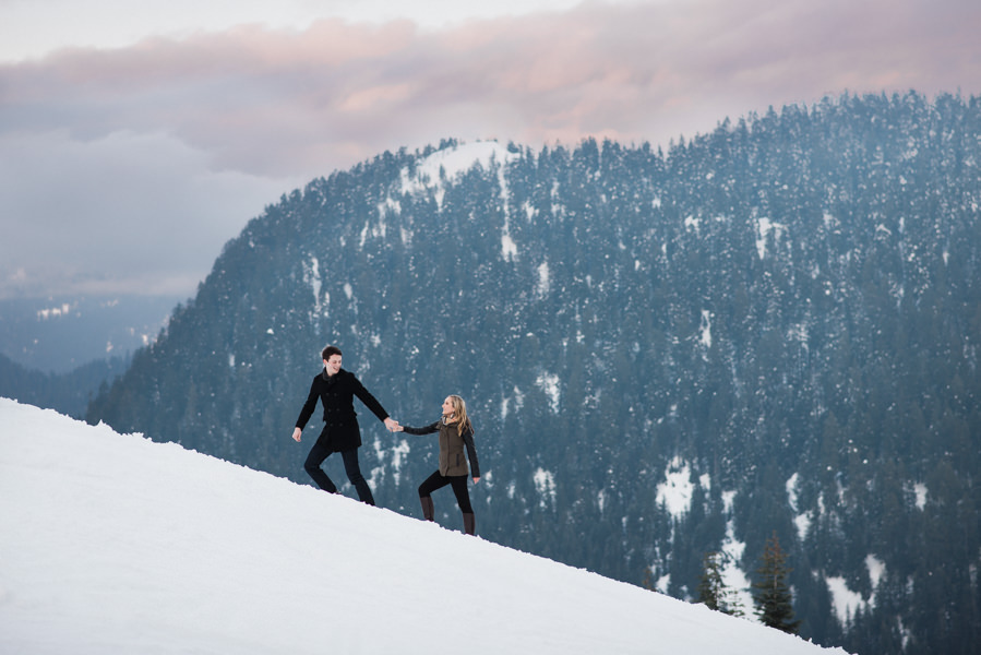 couple walking in snow on Grouse Mountain during engagement photos