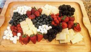 fourth of july chaucuterie board with raspberries, blackberries, blueberries, strawberries, extra sharp cheddar cheese, and mini marshmallows
