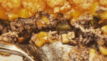 cowboy casserole is hamburger, string beans, corn, carrots, tater tots, and cheese in a creamy sauce