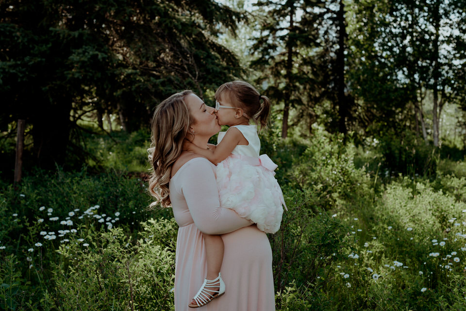 Photo of a toddler kissing her mom while sitting on her moms pregnant belly taken by maternity photographer in invermere jena lee photographs