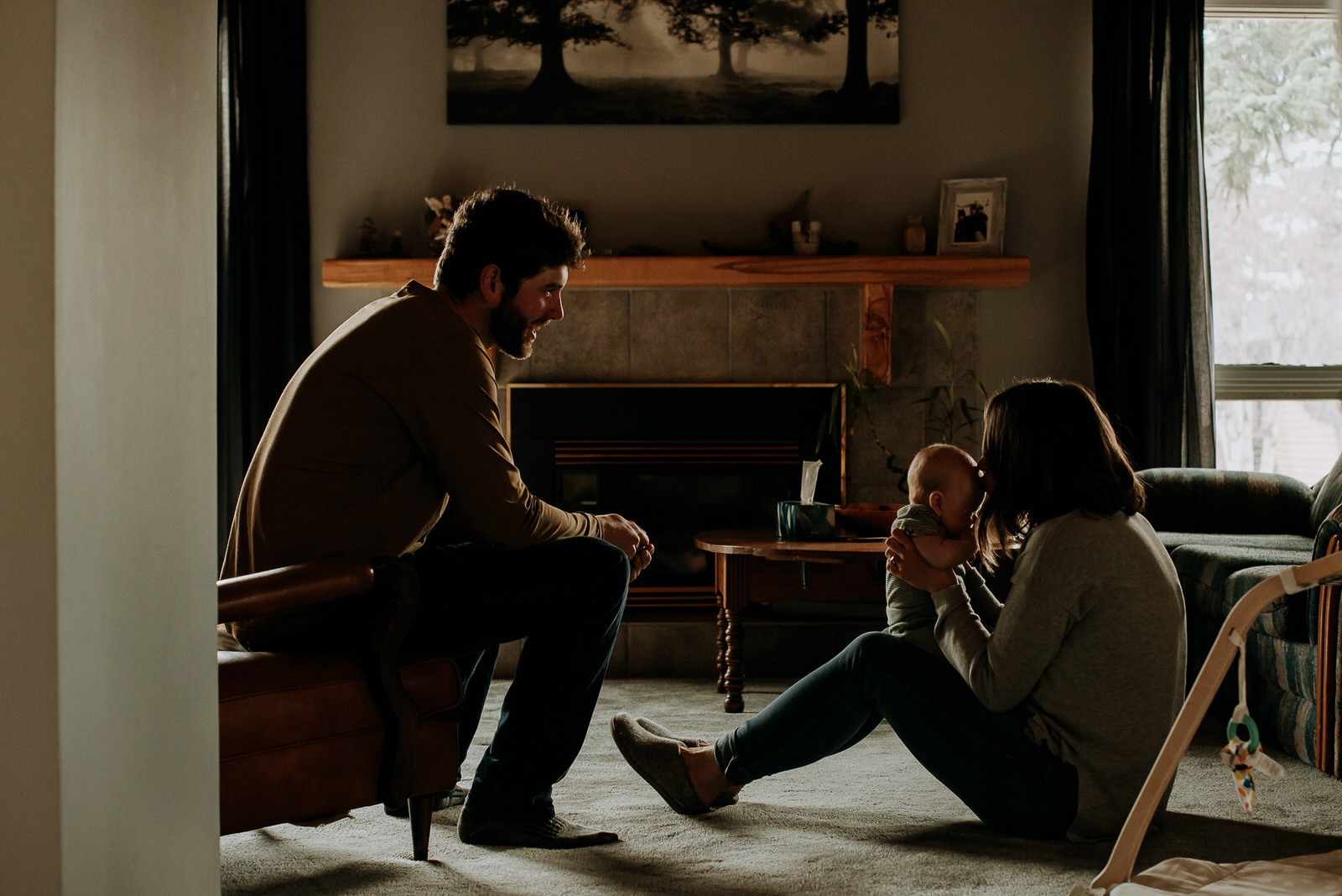 silhouette image of a family sitting in their living room on the floor with their baby during their in home family photography session in golden bc with jena lee photographs