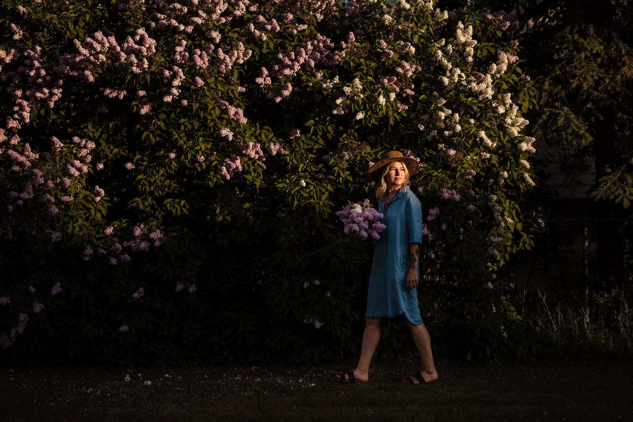 Portrait of Jena Mathews walking in front of a large lilac bush at sunset in Golden BC