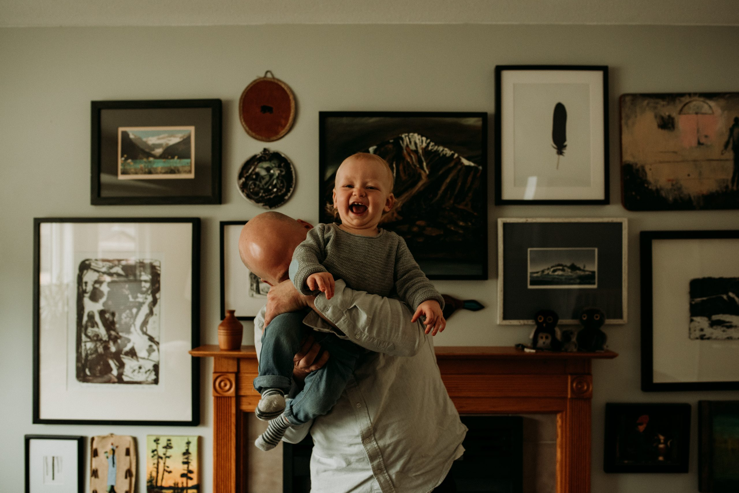 Photography of a dad holding his son up in the air and blowing on his back making him giggle during their family photography session with golden bc photographer jena lee photographs
