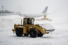 Heavy machinery clears the snow at LaGuardia Airport during a winter storm in New York