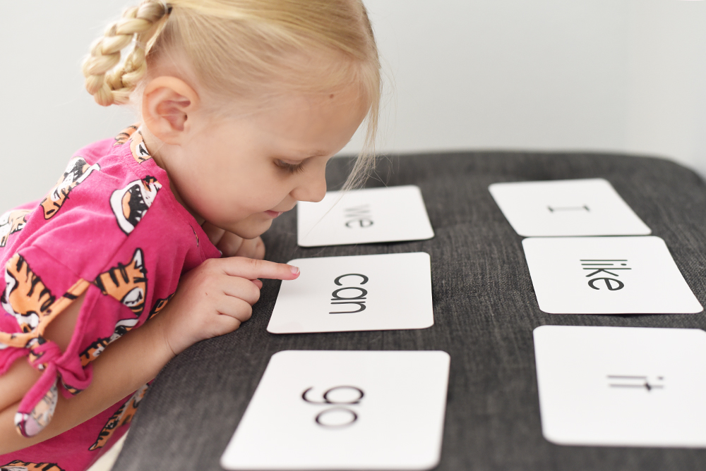 girl looking at sight word flashcards from the Kindergarten Toolkit