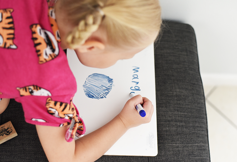 girl writing her name on a small white board