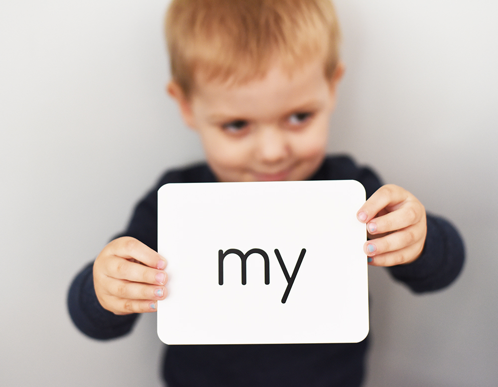 toddler boy holding card that says MY