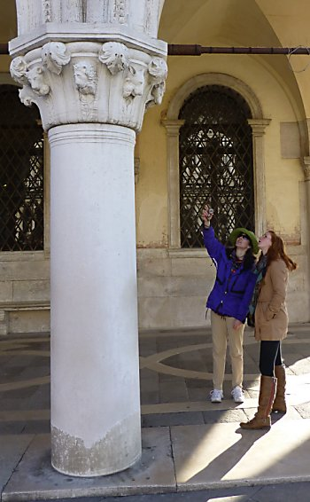Jen and Lexi study the predator/prey capital on the Palazzo Ducale.