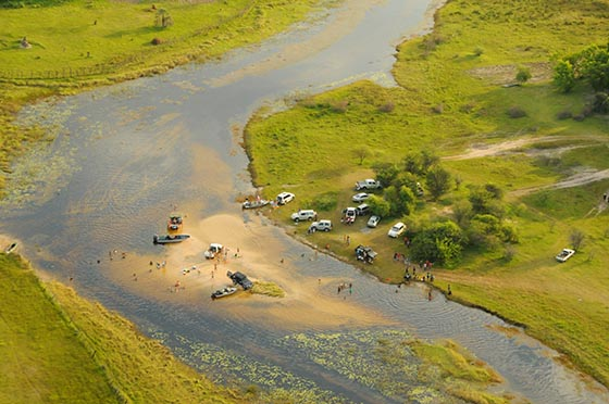 Cars and people gathered on a river.