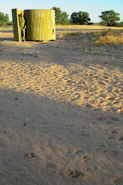 Mike in the outhouse door; lion tracks at the bottom of the image - Kgalagadi Transfrontier Park, photo by Mike Weber