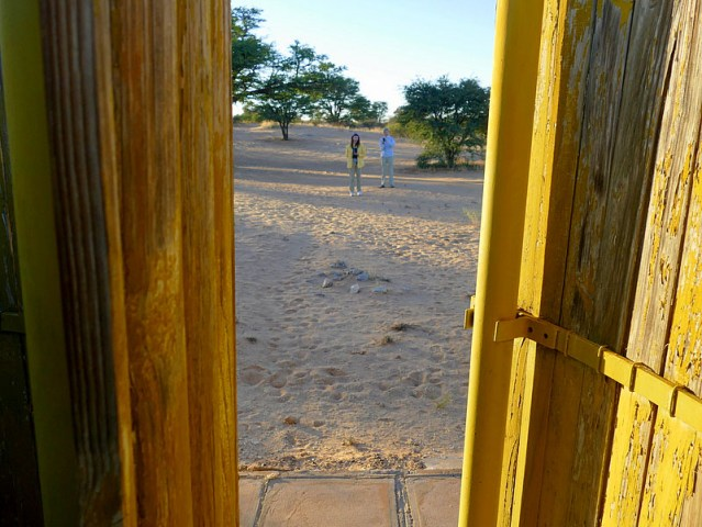 The view from the outhouse; Jen and Barb standing on lion tracks - Kgalagadi Transfrontier Park, photo by Mike Weber