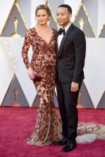 Chrissy Teigen e John Legend, vestido por Marchesa, jóias por Lorraine Schwartz, bolsa por Swarovski, relógio por Bulgari.