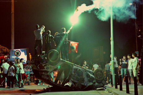 Protestors holding up a flare while standing on a destroyed car in Taksim Square.