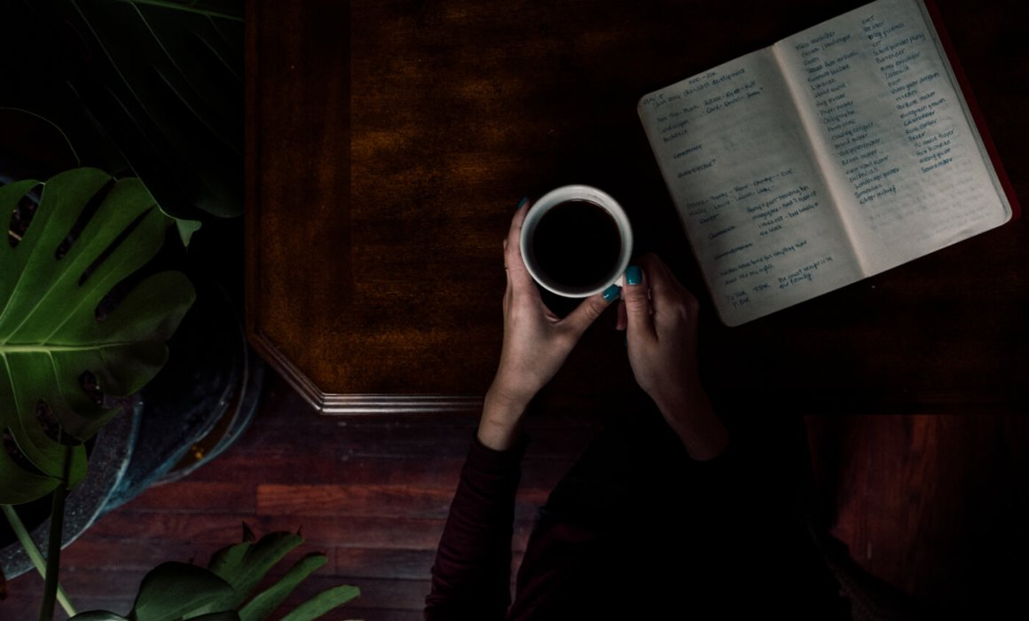 cup with hands and notebook on table