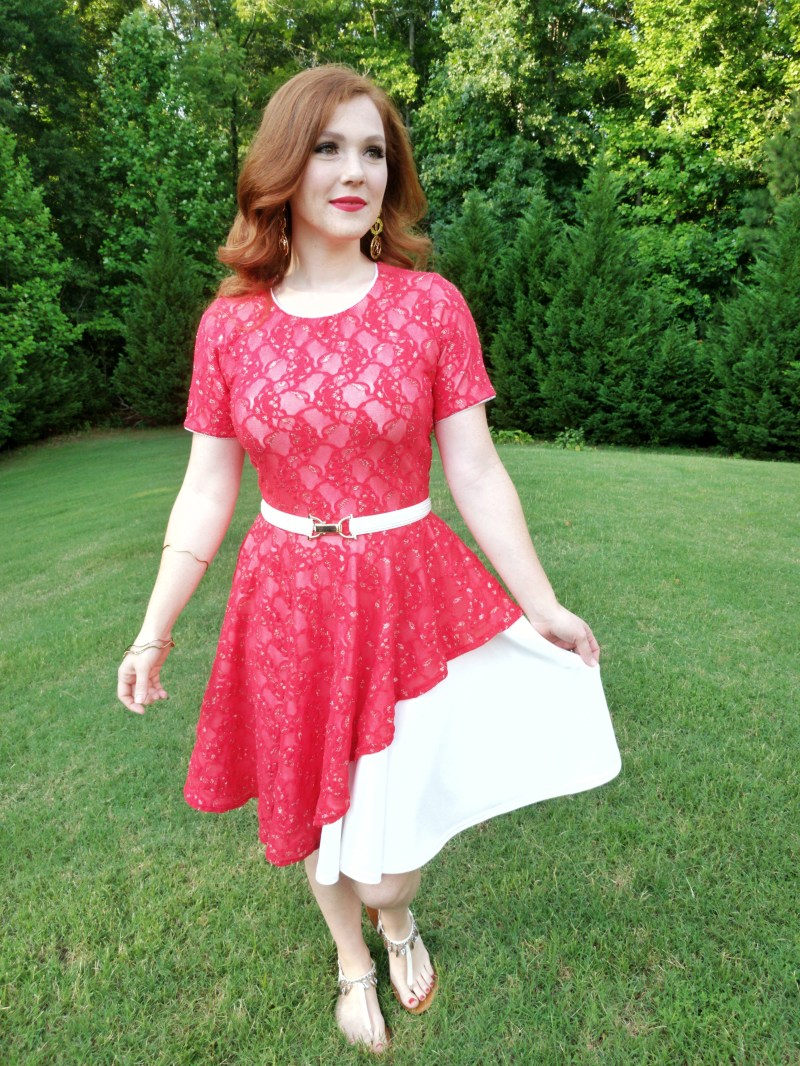 red lace overlay on white dress with an asymmetrical hem on the overlay