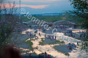 Residents in the Salta desert area spend a hot weekend picnicking and playing at a nearby river before summer rains cause the water level to rise.