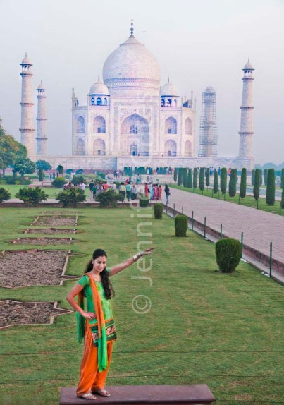 Indian girl poses in front of the Taj Mahal