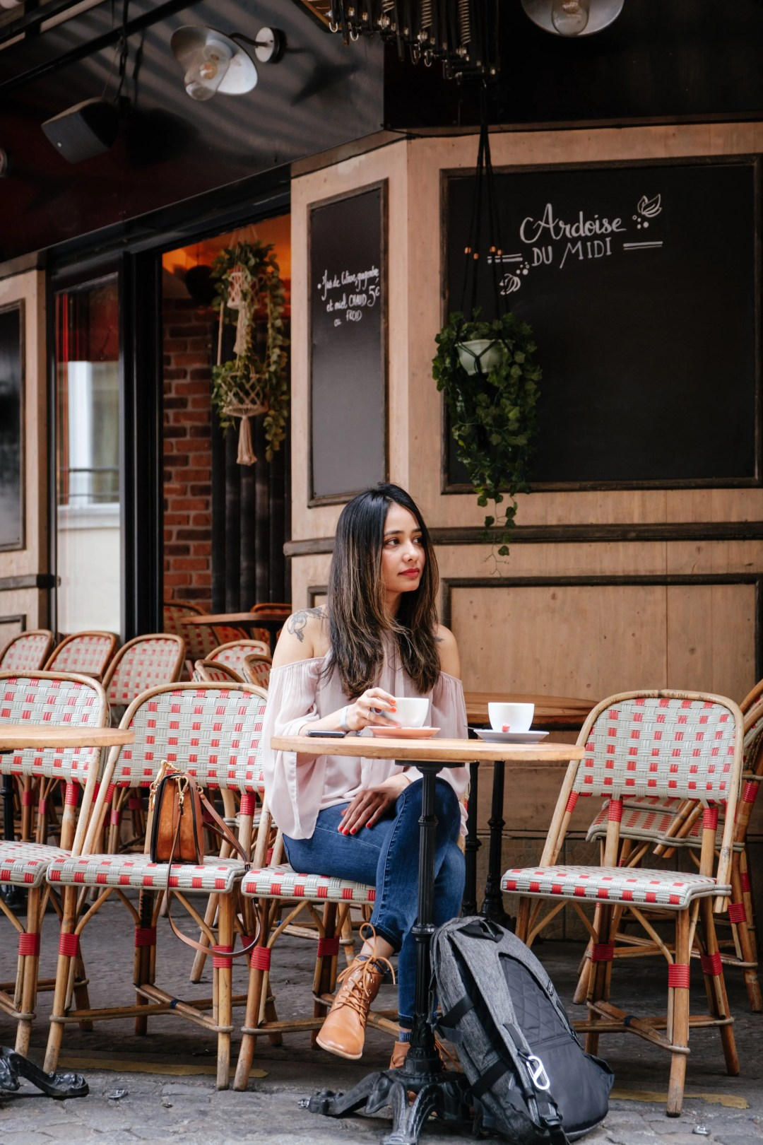 A woman sits in a coffee shop by herself with two cups of coffee. She has decided to start relationship counseling for singles in Dallas, TX with Rethink Therapy.