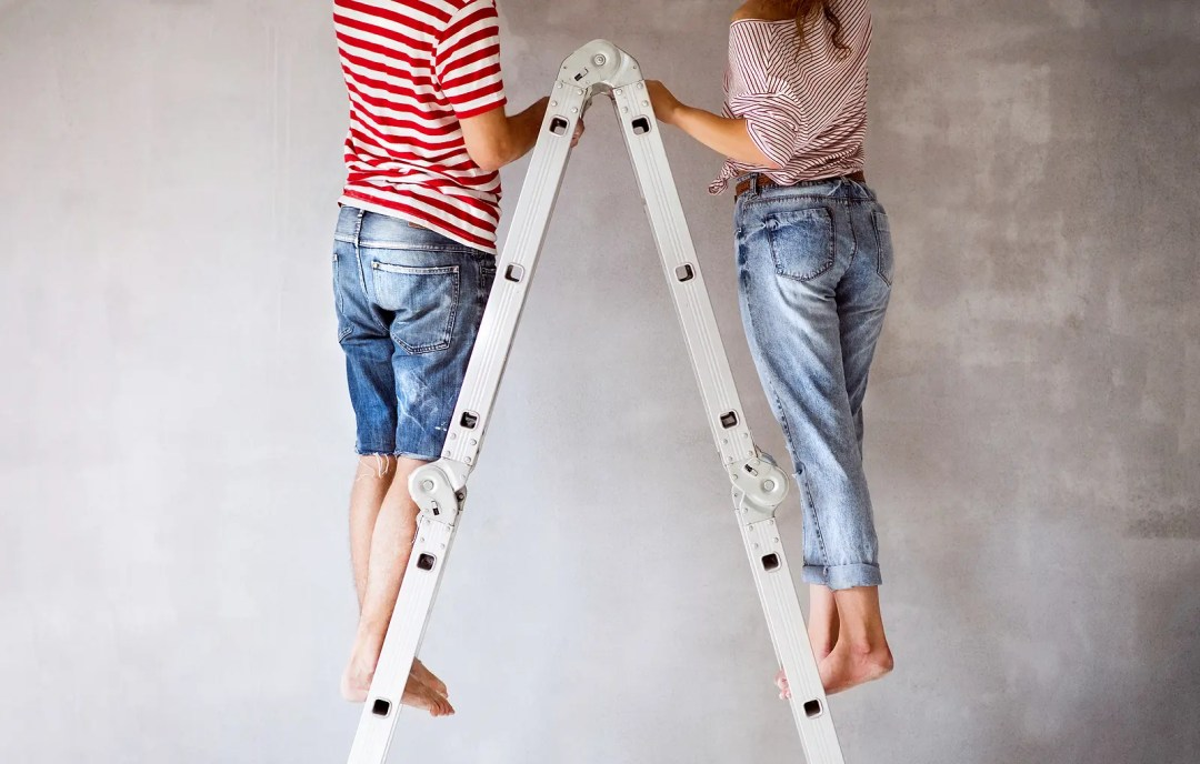 A couple stands on a ladder. This reflects concepts discussed in online marriage counseling in Dallas, TX with Rethink Therapy 75205.