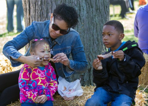 Tara Cowan feeds her granddaughter, Quinn Robinson, 2, a rib as grandson, Kaden Robinson, 7, looks on.