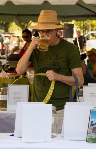 An attendee drinks a beer while reading about raffle prizes.