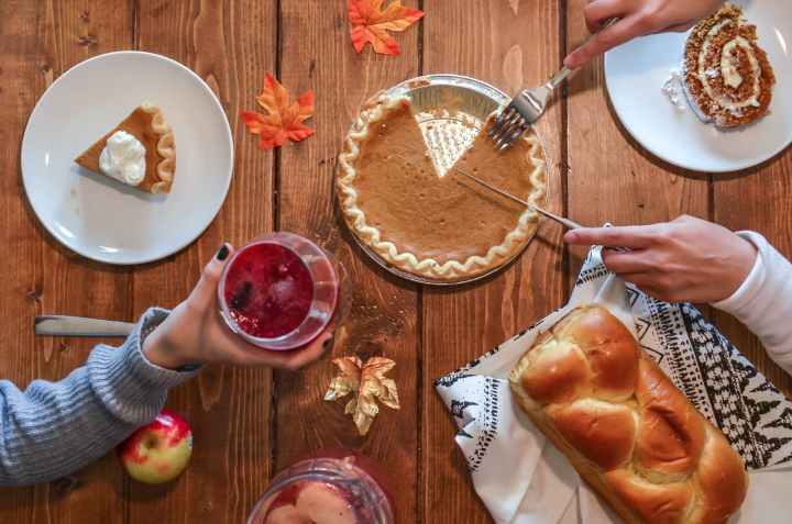 person slicing pie for holidays. enjoy favorites in moderation.