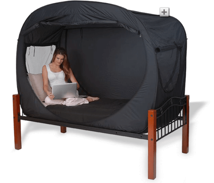 PRIVACY POP TENT IN BLACK WITH A GRIL ON LAPTOP INSIDE.