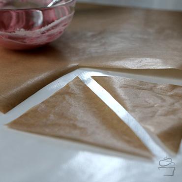 Ein Quadrat aus Backpapier ausschneiden und teilen, so dass zwei Dreiecke entstehen. Die Größe kann variieren, sollte aber noch handlich sein.