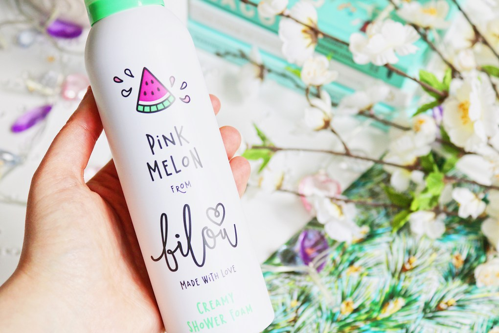 Close up photo of the bilou Pink Melon Shower Foam bottle with white flowers blurred into the background