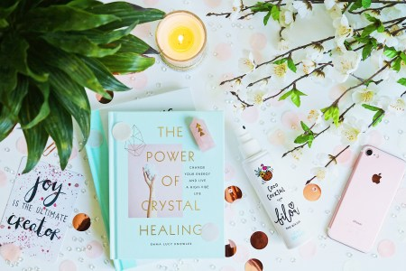 "5 Blog Recommendations: A flat lay consisting of a book titled 'The Power of Crystal Healing"", flowers, a candle, an iPhone and a bottle of bilou Coco Cocktail Bodyspray"